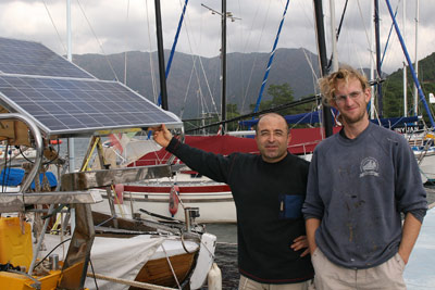 Macit, who wired the solar panel for free and donated a regulator, and Sam stand next to the solar panel mount, built and installed for cost by Demir Marine